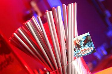 Foto zeigt Strohhalme mit Flyer, Foto: Tom Wenig