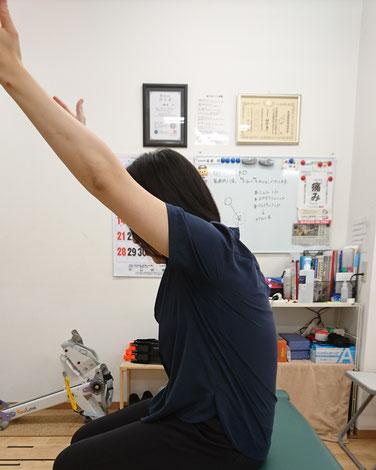 ウチの嫁さん。猫背の状態で腕を上げるとこれくらい。肩辺りがかなりキツイらしいです(^^;)