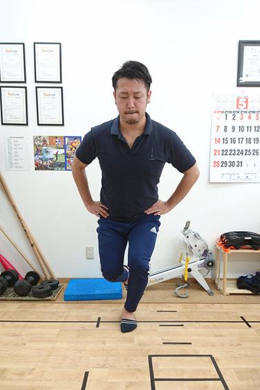 当院で足の痛みや歪みをチェックする際に行う「片足スクワット」。つま先と膝は真っすぐ向けた状態で、しゃがんでいきますが、膝は内側に入らないようにするのと、身体は真っすぐを保ちながらやります。股関節・膝・足首を線で結んで真っすぐなのが理想。