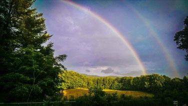 Regenbogen in einer Landschaft als Beispiel für Lichtbrechung