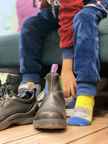 Kinder & Jugendliche - Junge zieht Schuhe an
