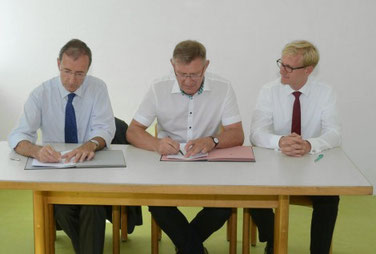 Vertragsunterzeichnung auf der Baustelle: Dr. Jochim Schulz, OB Michael Beck, Dr. Jens von Lackum.