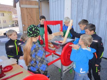 Kindergruppe beim Herstellen von Süssmost.