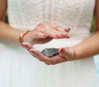 Cérémonie laïque des pierres. La mariée magnétise sa pierre. Elle tient une pierre dans sa main gauche et la magnétise de sa main droite. Elle porte un vernis à ongles vieux rose.