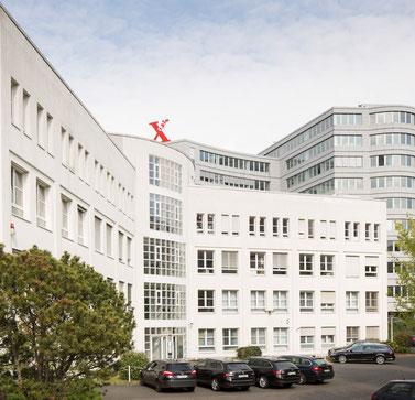 Praxisgebäude von außen mit Parkplatz