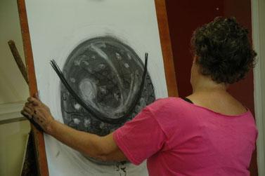 Een vrouw, op haar rug gezien, tekenent met houtskool op een groot formaat papier.