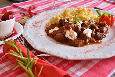 Wildgulasch und Spätzle auf Teller angerichtet auf einer rotweiß karierten Tischdecke