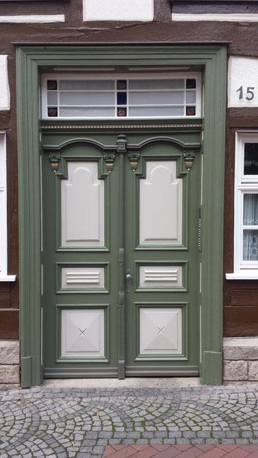 Tür eines Fachwerkhauses in grau mit hellgrauen Absetzungen und Oberlicht