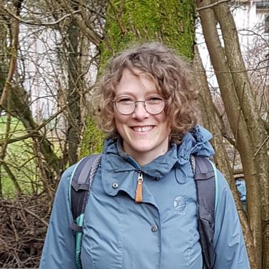 Hanni Schnell steht mit Rucksack und Outdoorjacke im Wald und lächelt den Betrachtenden freundlich zu.