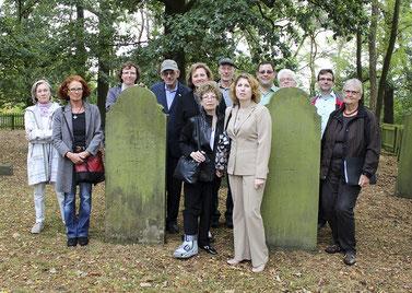 Nachfahren der Familie Löwenberg sind nach Rehburg gekommen – und lassen sich von Mitgliedern des Arbeitskreises Stolpersteine die Gräber ihrer Vorfahren auf dem jüdischen Friedhof zeigen.