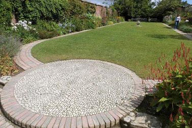 Exklusive Pflasterarbeiten wie dieses Rondell mit anschliessenden Wegen geben einer Gartengestaltung nicht nur einen Blickfang, sondern auch Struktur.