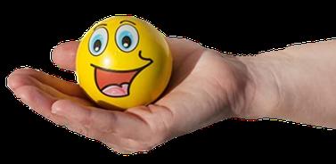 Zu sehen ist eine geöffnete Hand, in der ein Knautschball mit einem lachenden Gesicht liegt. Ein Knautschball zeigt resilientes Verhalten, weil er immer wieder seine Ursprungsform einnimmt.