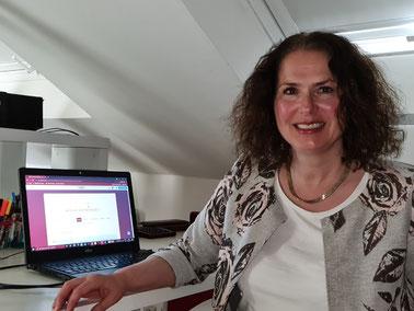 Miriam Pietrangeli sitz am Schreibtisch und schaut freundlich in die Kamera