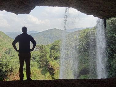 Ein Wasserfall stürzt vor der Höhle in die Tiefe