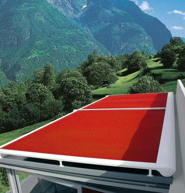 """Wintergartenmarkise """"XLINE"""" mit rotem Stoff an einem Haus in den Bergen"""