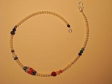 Umgestaltung einer Zuchtperlenketten durch Einarbeitung einer Künstler Glasperle und dazu farblich abgestimmte Edelsteine.