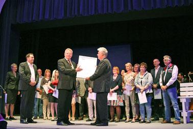 Rolf von Bloh übergibt die Zertifizierungsurkunde zur allergikerfreundlichen Kommune an Bürgermeister Dr. Wolfgang Honsdorf im Beisein der ebenfalls zertifizierten Betriebe