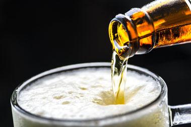 Bier fließt aus Flasche in Glas