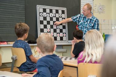 Lehrer vor der Tafel erklärt den Kindern Schach
