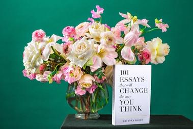 ガラスの花びんいっぱいに活けられたバラ。傍らに置かれた書籍。