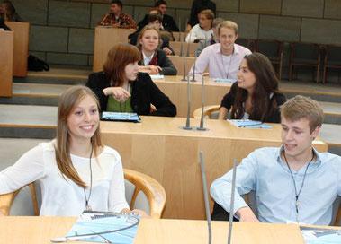 Luise Kixmöller (vorne links), Naomi Baba (Mitte rechts) und Leonard Meyer-Schwickerath (Reihe 3 rechts) erkunden den Plenarsaal.