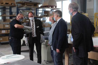Holm Pfeiffer führt dem Gießener Regierungspräsidenten, Kreishandwerksmeister Ralf Jeschke, Aßlars Bürgermeister Christian Schwarz und Ulrich Leber von hessenTischler (v.l.) die Eigenschaften von Corian vor.