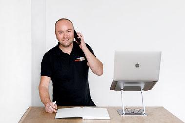 Sebastian Krebs hält Telefon in der Hand