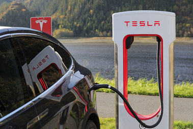 Heck eines schwarzen Tesla, der gerade an einer Ladesäule aufgeladen wird. im Hintergrund ein See, die Ladesäule spiegelt sich in den Scheiben des Autos