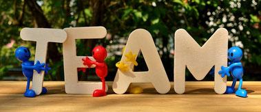 Bild von vier bunten Figuren, die die Buchstaben T E A M halten