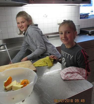 Mädchen waschen Geschirr, nachdem sie die gesunde Jause vorbereitet haben.