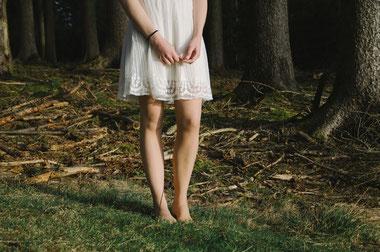 Frau in weißem Kleid steht im Wald barfuß