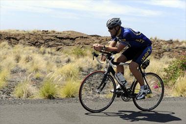 オークリーのスポーツサングラスをかけロードバイクに励む男性