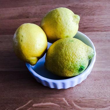 Drei Zitronen in einer kleinen weißen Tartelette-Form.