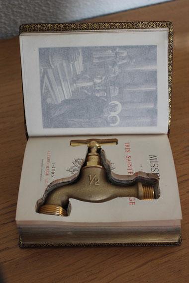 Oeuvre d'art de Laurent Valera sur le manque d'eau en Afrique du Sud. Robinet caché dans une bible.