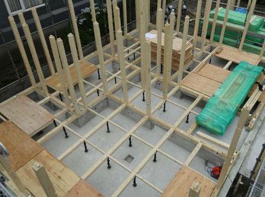 木造軸組工法の新築工事中の床下。床下にはコンクリートが打たれ、束が大引きを支え、たくさんの柱が立っています。整理整頓された、とてもきれいな工事現場です。