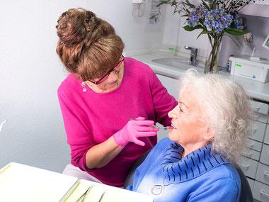 Zahnarztpraxis Dr. med. dent. Alina T. Ioana. Angestellte Zahnärztin berät und behandelt Seniorin.