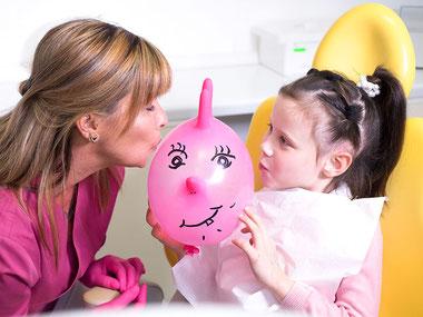 Zahnarztpraxis Dr. med. dent. Alina T. Ioana. Kinderzahnheilkunde. Zahnmedizinische Fachangestellte lenkt Kind mit selbstgemachtem Spielzeug ab.
