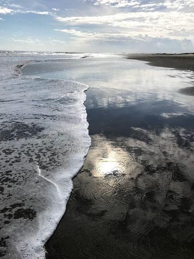 波と海岸にうつる太陽