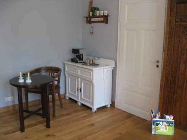 Raumecke mit Holzdielen, alter Waschtisch in weiß lackuert, weiße Füllungstür, antiker Tisch mit Stuhl