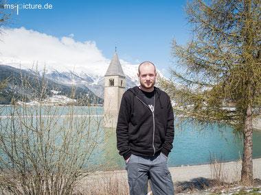 Matthias Schreyer vor dem Reschensee am Reschenpass