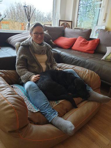 Nina Hoffmann mit Hündin Emily im Hundekorb kuschelnd