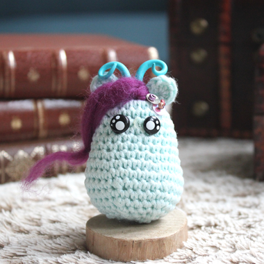personnage totem fantastique ondine, bleu glace avec des cornes et des paillettes, fait à la main au crochet