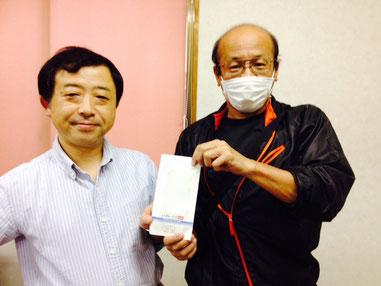 診療所建設呼びかけ人の橋本光一さん(左)が受け取りました