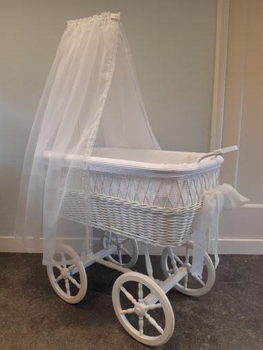 Deze rieten wieg op wielen is opnieuw in de verf gezet en daarna bekleedt met witte wafelstof. Het hemeltje en de strik zijn gemaakt van een fijne bruidstule.