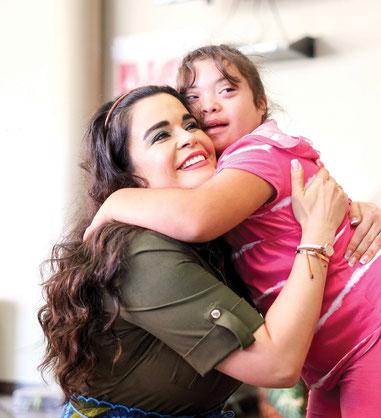 Junge Mutter hält Mädchen mit Down-Syndrom im Arm