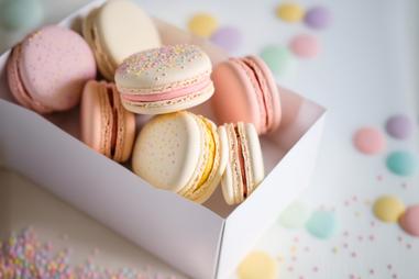 ハート形のピンクのマカロンとミルクティー。キラキラボールペンとノート。