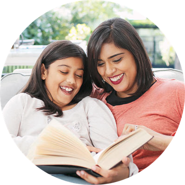 mother and daughter reading book together in living room