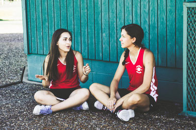 Two young women speaking to each other. They seem to be teammates, and are hopefully practicing mindful listening together.