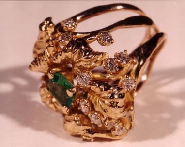 Une bague en or, avec une émeraude et des diamants est vue de profil.