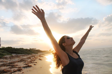 Frau am Strand streckt Arme in die Luft - rasierte Achseln